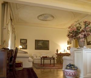 Mobili antichi, tappeti pregiati, complementi d'arredo particolari. Sul soffitto la decorazione firmata Mariani si ispira a uno stile decorativo neoclassico di grande eleganza