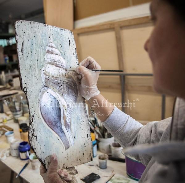 L'artista dipinge a mano libera sulla tavola in legno antico
