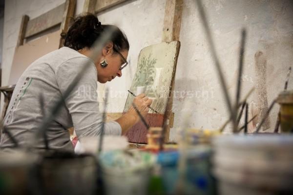Dietro i barattoli con i colori, osserviamo l'artista mentre dipinge