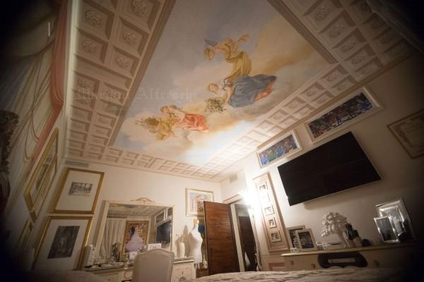 Un soffitto decorato a finti cassettoni e con figure classiche nel cielo, dipinto da Mariani per una camera da letto speciale