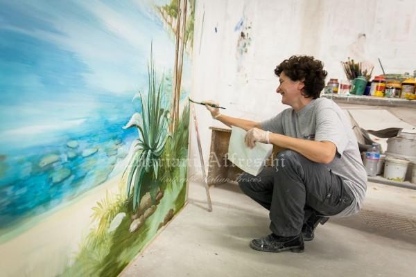 Una fase dell'esecuzione del dipinto. Il verde della vegetazione bilancia la profondità della veduta mediterranea