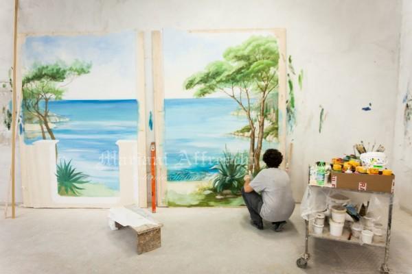 Nel laboratorio di Mariani Affreschi, l'artista dipinge il trompe l'oeil sui due pannelli che saranno poi collocati nella casa del cliente