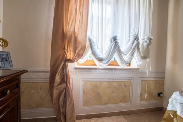 Dipinta a mano dagli artisti di Mariani, la boiserie in finto marmo alla base delle pareti si sviluppa sul perimetro della stanza e riempie spazi importanti, conferendo agli interni equilibrio ed eleganza