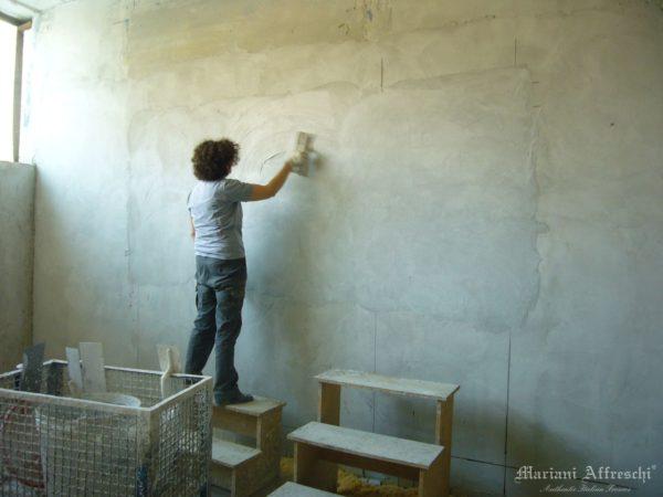 Nel laboratorio di Mariani Affreschi, l'artista stende l'intonaco prima di dipingere l'opera commissionata dal cliente