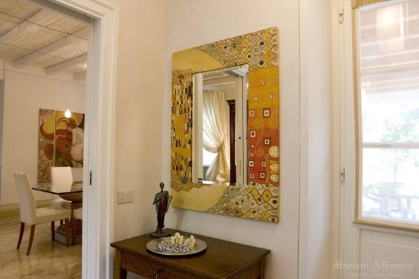 A mirror becomes a unique décor item when adorned by a beautiful frame. The fresco frame in this photo is inspired by Klimt motifs