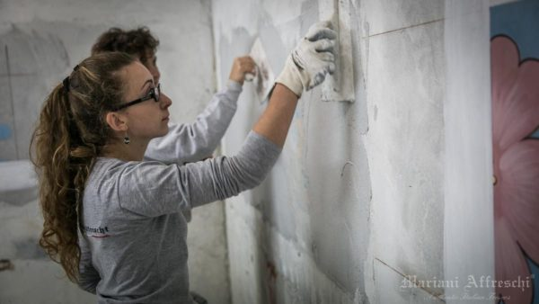 A young artist specialised in the fresco technique prepares the plaster support on which to execute the work