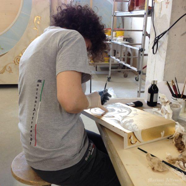 L' artista di Mariani impegnata nella decorazione a foglia oro del cappello della boiserie