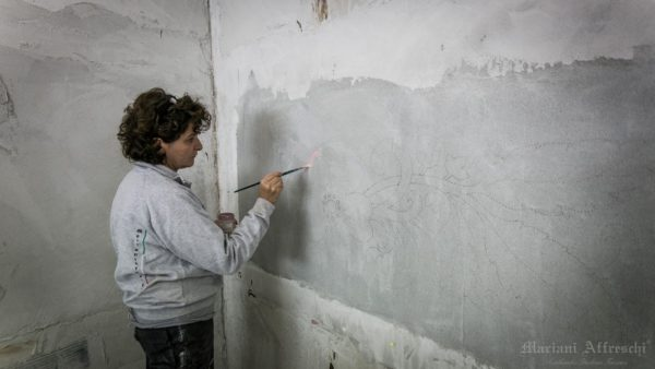 The artist starts painting the fresco on the wet plaster