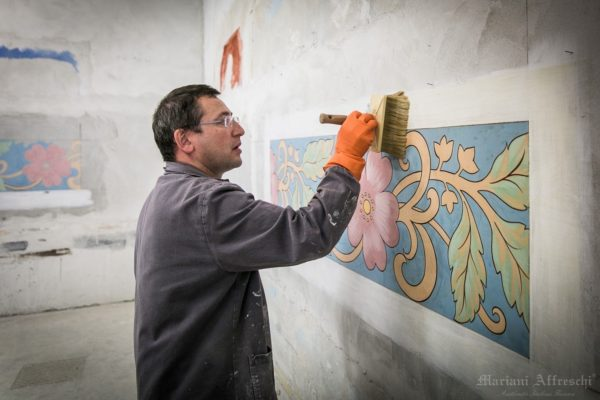 The technician applies glue on the fresco after the plaster has dried