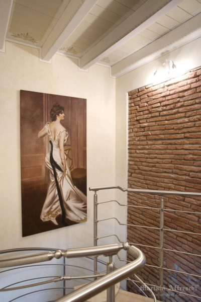 The Black Sash, a work by Boldini frescoed by Mariani. The classic fresco painting, antique wall with exposed bricks and stainless steel railing blend beautifully in this stairwell