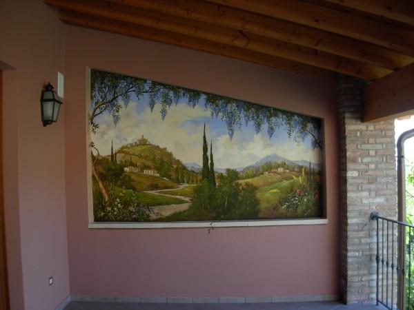 Lo scorcio di un paesaggio in un affresco firmato Mariani sotto il portico di una villa
