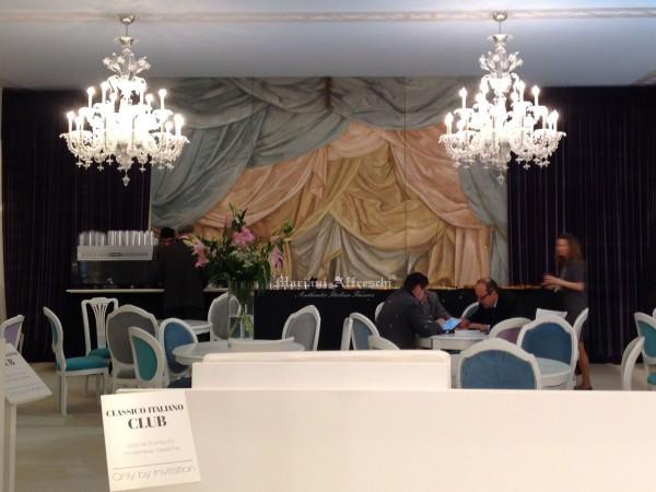 Un grande affresco realizzato da Mariani crea l'effetto trompe l'oeil di un tendaggio teatrale. In questa immagine ci troviamo nell'area Lounge del Gruppo Classico Italiano, di cui fa parte Mariani Affreschi. Si tratta di una zona relax per i clienti del gruppo in visita al Salone del Mobile