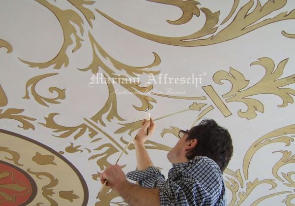 Un artista completa il profilo dei decori in oro su un soffitto a cupola