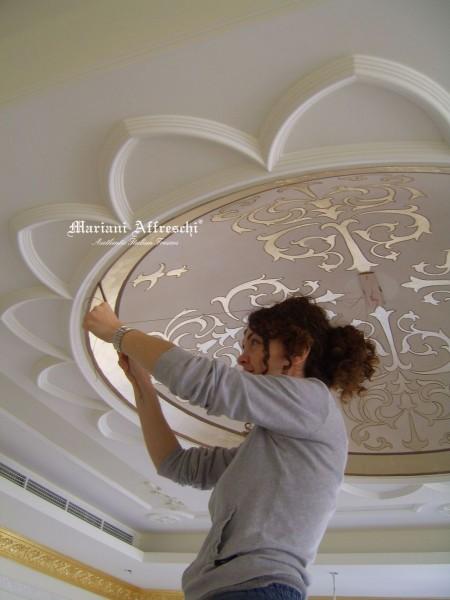 Un'artista del team Mariani traccia con attenzione i decori in oro di una cupola