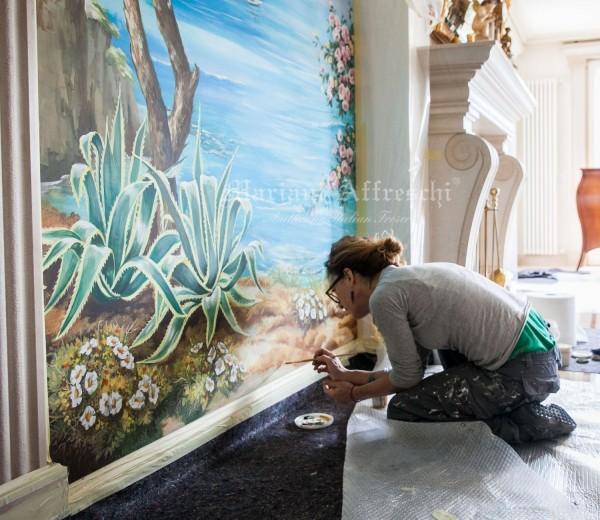 Dopo aver incollato il pannello alla parete del soggiorno, la decoratrice di Mariani ritocca alcuni dettagli