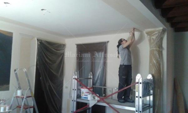 Una fase preparatoria del fregio a soffitto, dipinto dagli artisti di Mariani in armonia cromatica con la sala
