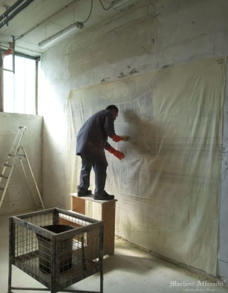 Il tecnico di Mariani incolla la tela sull'affresco finito, secondo l'antico metodo Calicot