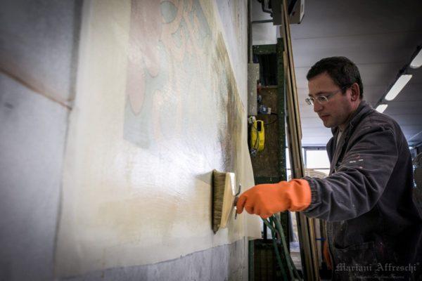 Una tela viene stesa sull'affresco, prima di strappare l'opera