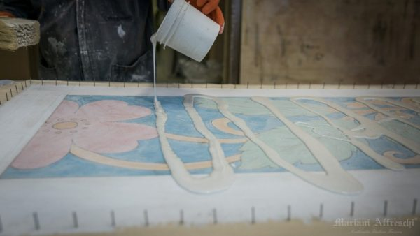New glue is applied on the negative side of the fresco to transfer it to positive